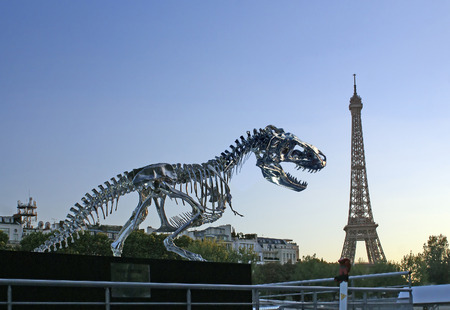 tyrannosaur: PARIS, FRANCE - SEPTEMBER 22, 2013: Sculpture Tyrannosaur in Paris on the river Seine on background of the Eiffel Tower. Sculptor Philippe Pasqua