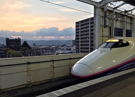 High-speed train is at the platform of the railway station of Fukushima on backgroubd of the sunset