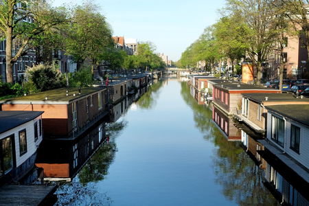 AMSTERDAM, NETHERLANDS - MAY 14, 2017: Houseboat on the canal in the historic part of Amsterdam