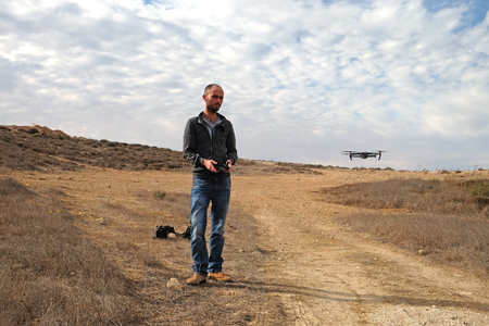 Young man launches a drone over a desert area