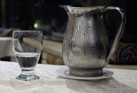 Misted metal jug with cold water and a glass on the table