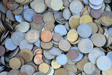 BEER SHEVA, ISRAEL - JANUAR 04, 2019: Scattering of coins from different countries on the junk shop counter Редакционное