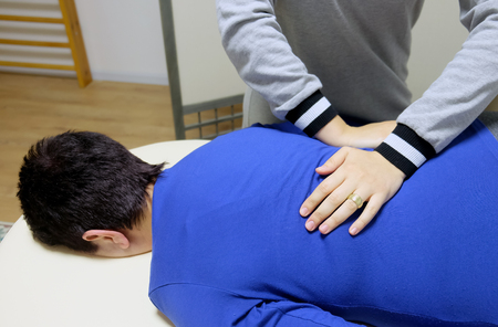 Physical therapist produces a manual effect on the client in the prone position Banco de Imagens