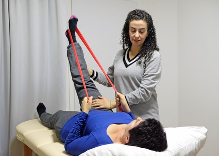 Physical therapist shows exercises for legs in the supine position