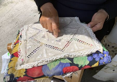 LEFKARA, CYPRUS - MAY 10, 2019: Craftswoman embroiders a napkin and shows a knot named after Leonardo da Vinci Éditoriale