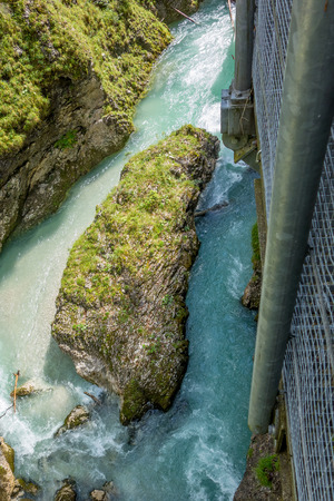 eagle canyon: Big rock in the river ache as seen from the steel boardwalk in the Leutaschklamm canyon in Bavaria, Germany  Tyrol, Austria Stock Photo