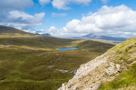 View of Lochan Fhionnlaidh and Canisp from hiking trail at Knockan Crag in North West Highlands Geopark, Scotland