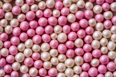 Closeup of one layer of pink and white sugar pearls (cake decor), from above