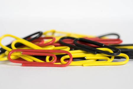 Heap of yellow, red and black paper clips on white background