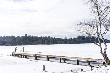 Stage in of frozen Kirchsee lake, Bavaria, with Alps in background,  in winter