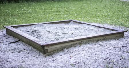 Prosta drewniana piaskownica na placu zabaw