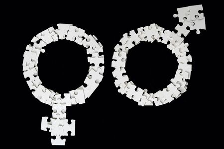 White Male and Female Signs made from puzzle pieces on black background