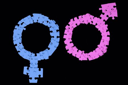 Pink Male and blue Female Signs made from puzzle pieces on black background