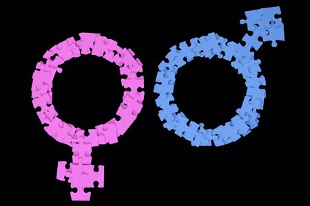 Blue Male and Pink Female Signs made from puzzle pieces on black background Standard-Bild