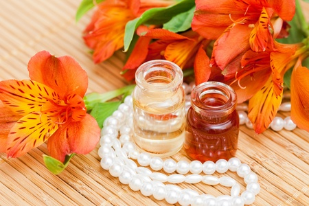 Aromatic oils, alstroemeria flowers and beads of pearls photo