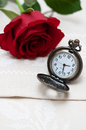 Red Rose and a pocket watch on a napkin embroidered with a cross photo