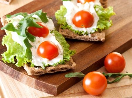crispbread: Pane croccante con pomodorini formaggio, lattuga e ciliegio Archivio Fotografico