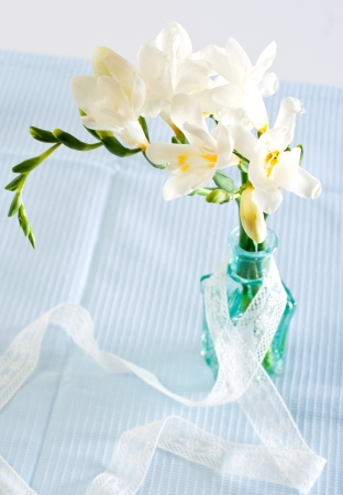 White freesia flowers in decorative bottles Reklamní fotografie