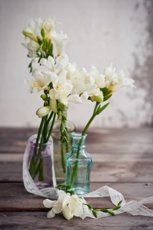 White freesia flowers in decorative bottles photo