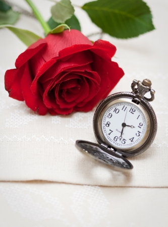 Rose roja y un reloj de bolsillo en una servilleta bordada con una cruz photo