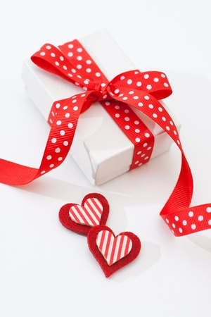 White gift box with red ribbon on red background photo
