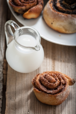 Cinnamon rolls and Bun with poppy seeds on a plate and small jugs of milk photo