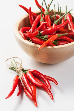 Red Hot Chili Peppers in bowl on white background photo