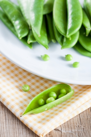 Pods of green peas on a white plate photo