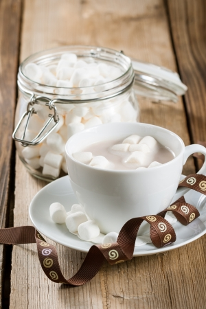 Marshmallows in a cup of Hot Chocolate on a wooden table photo