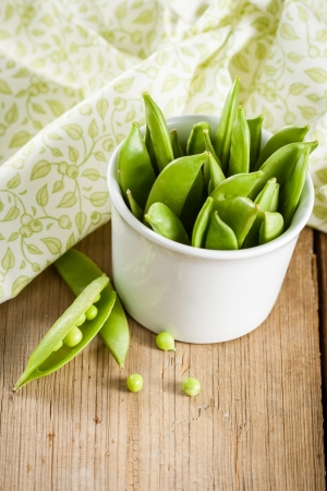 Pods of green peas in white bowl photo