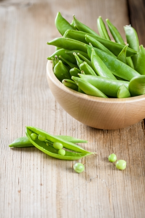Pods of green peas in a wooden bowl photo