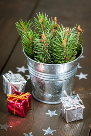 Spruce branches in a small bucket and decorative gift boxes photo