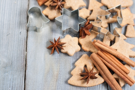 Gingerbread cookies and spices over wooden background photo