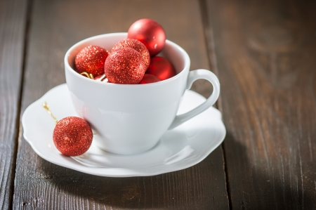 Small red Christmas balls in a white cup photo