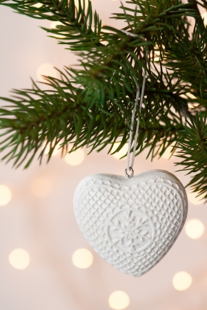 White heart shaped Christmas decoration on the tree photo