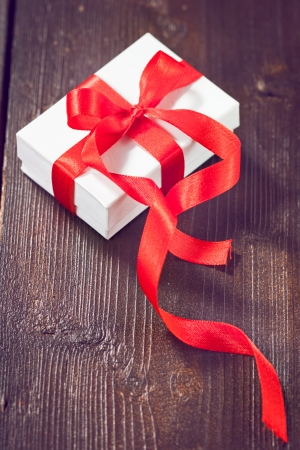 White gift box with red ribbon on wooden background photo