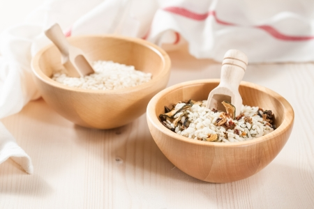 Mix of raw rice and dried vegetables in wooden bowls on a light background photo