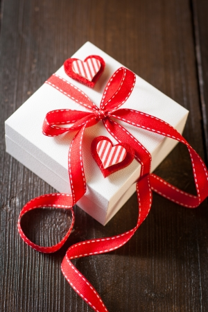 Holidays gift and hearts on wooden background Valentines day background photo