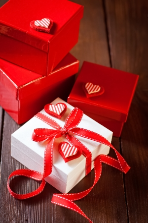 Red and white gift box and hearts on the wooden background photo
