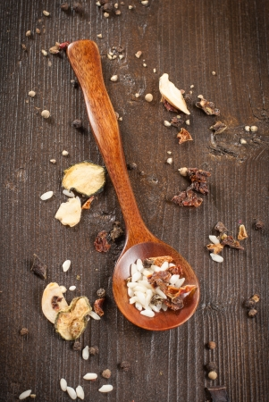Mixture of raw rice and dried vegetables in wooden spoon photo