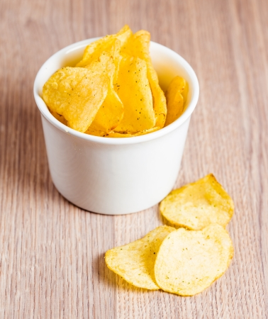 Potato chips in white bowl on wooden background photo