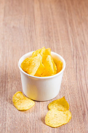 Potato chips in a white ceramic bowl on the table photo