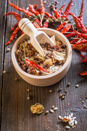 Mixture of raw rice and dried vegetables in wooden bowl on a textile  photo