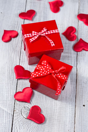 Red gift boxes on white wooden background photo