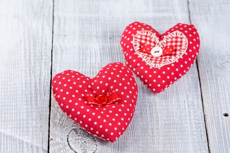 Two handmade red Hearts on white wood background photo