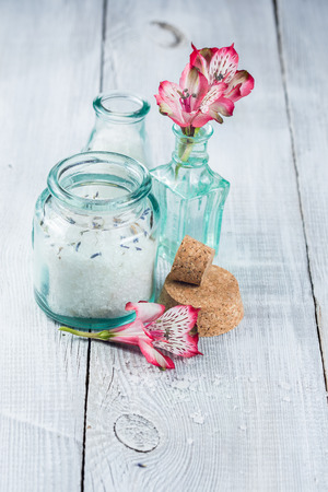 Jars with sea salt and flowers alstroemeria on a wooden white background photo