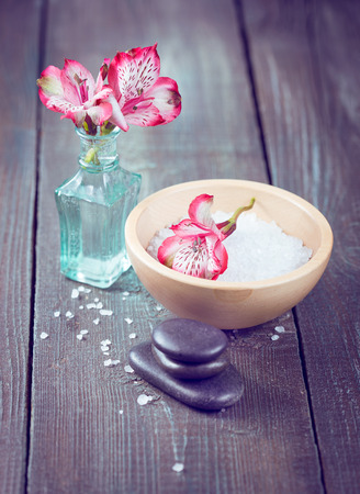 Spa stones, sea salt and flowers alstroemeria on a wooden background. Vintage color toning. photo