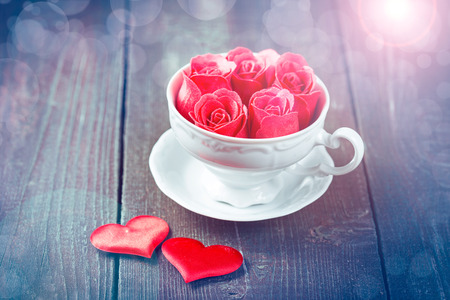 Pink roses in a cup on wooden background. Vintage color toning. photo