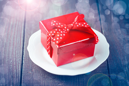 Red gift boxe on dark wooden background. Retro color toning. photo