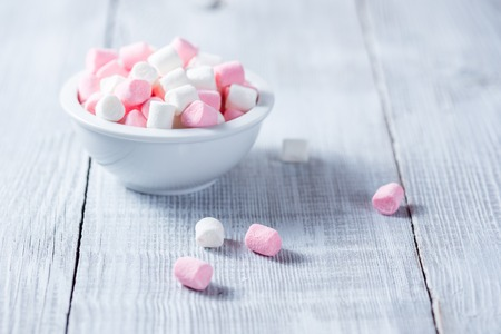 colores pastel: Malvaviscos rosa y blanco en Bol, sobre fondo de madera.